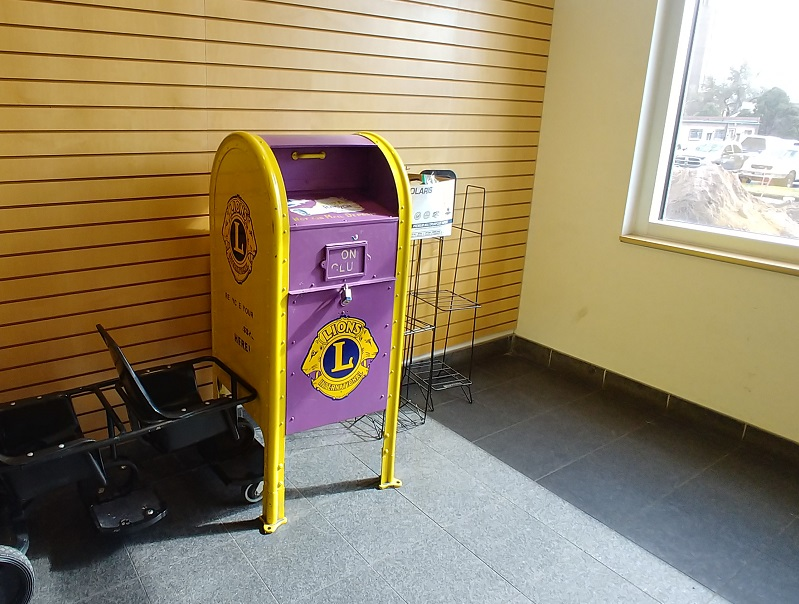 Yellow and purple painted mailbox to donate gentlly used eyeglasses and hearing aids